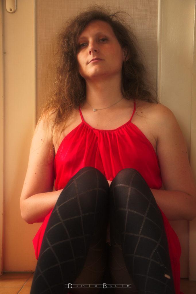 Moi, adossé à une porte, sur le sol, les jambes repliées vers le ventre, les bras entre mes jambes et mon ventre. Visage neutre.